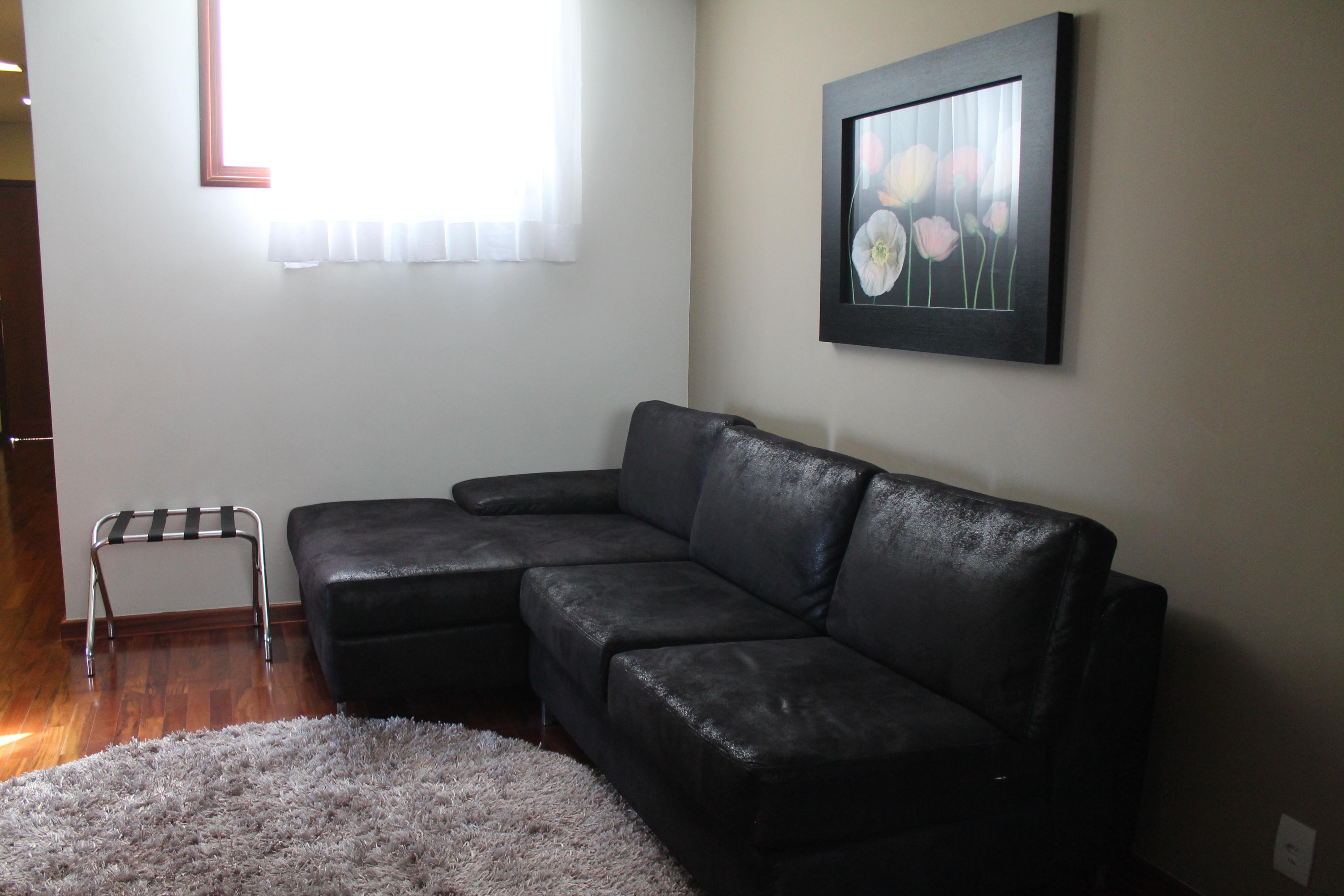 Sala ampla com sofá cama, televisão e frigobar