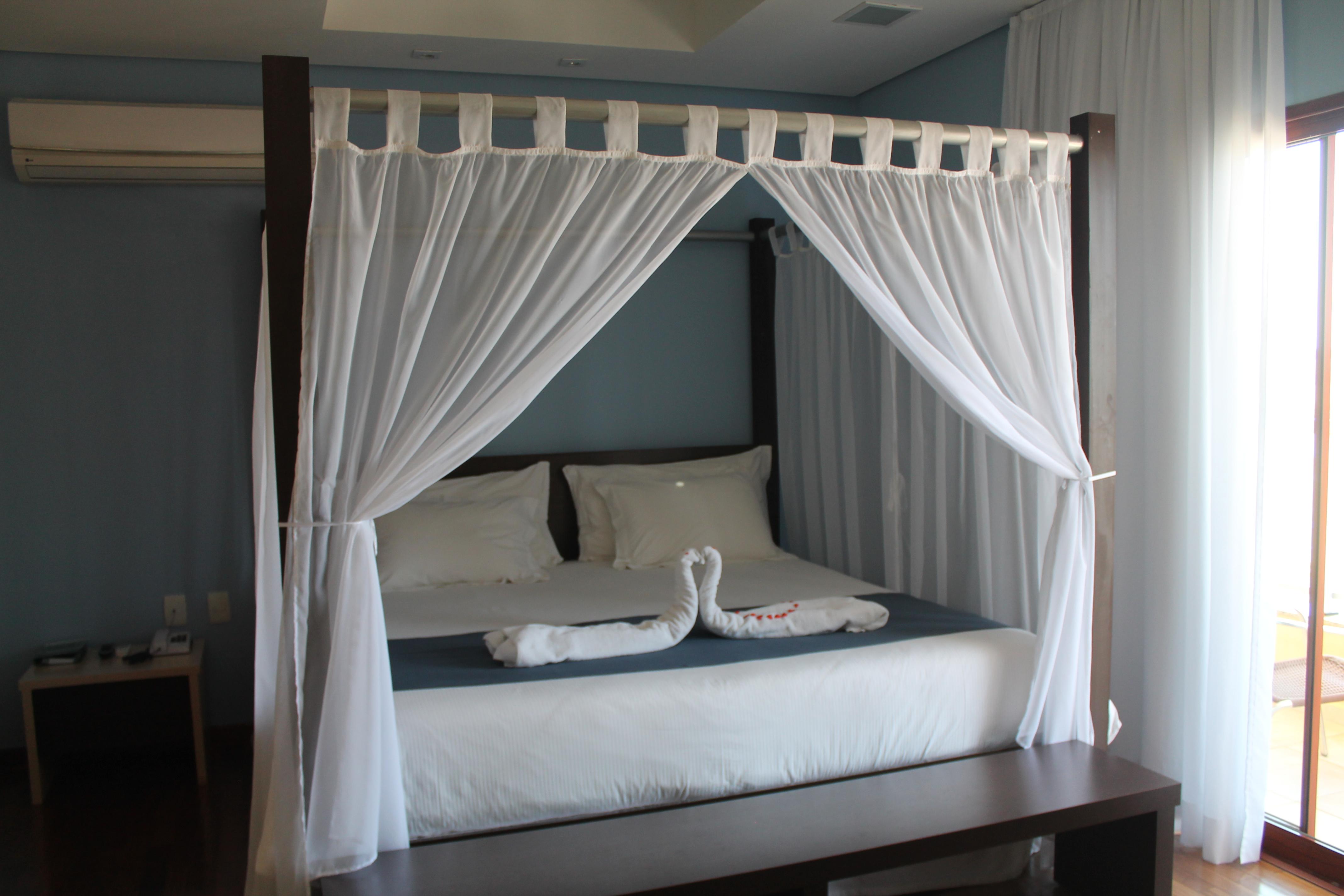 Quarto com cama king, dossel e teto solar